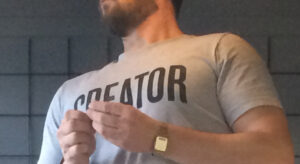Man wearing a t-shirt with the word Creator printed on it